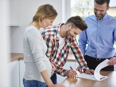 Couple signing a real estate contract with their agent