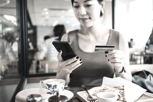 Woman managing online banking with smartphone and making mobile payment with credit card on hand while having meal in a restaurant