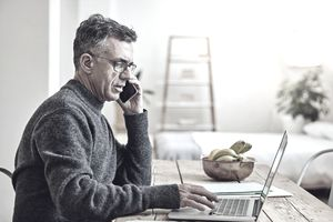 A man wearing a sweater speaks into his cell phone while sitting at a table and looking at a laptop