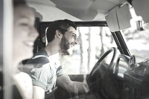 Side view of happy couple enjoying road trip