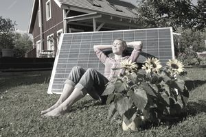 Woman relaxing in garden with solar panels in eco friendly home