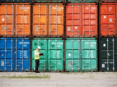 A customs inspector standing and reviewing a tack of containers