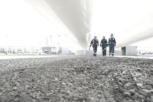 Workers walking below tanks at gas plant