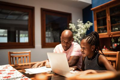 father and daughter sitting at kitchen counter discussing finances in front of computer