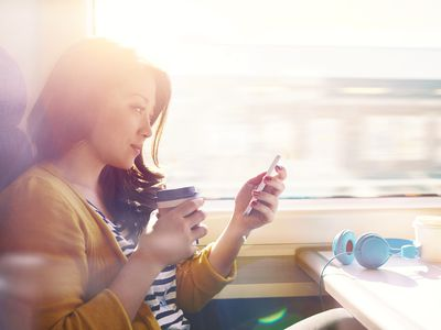 Woman on a commuter train looking at her phone.