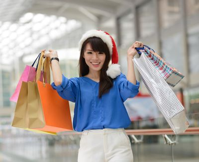 a young woman holding up shopping bags and wearing a Santa hat