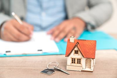 Person signing legal trust documents with a small house model an key sitting nearby.