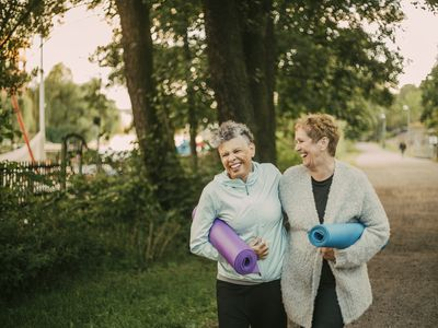 Smiling friends carrying exercise mats