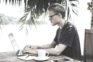 Young Man and Laptop in Tropical Setting