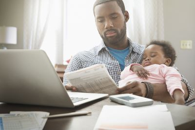 A father holds his baby daughter while looking at a bank statement, concerned