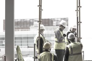 Workers on construction site discuss. - stock photo