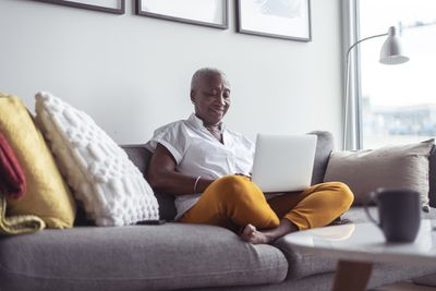 A homeowner sits on a couch looking at reverse mortgage requirements on a laptop.