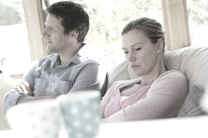 Couple sat Down Looking Angry - Stock Photo