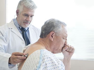 Doctor examining a coughing patient in hospital gown.