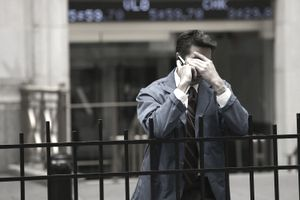 Man on phone on Wall Street looking distressed