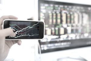 Checking stock prices on a smartphone and on a computer.