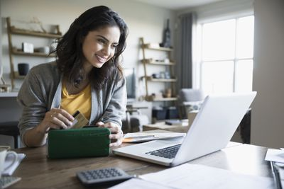 Smiling young woman with credit card and laptop paying bills online in dining room.