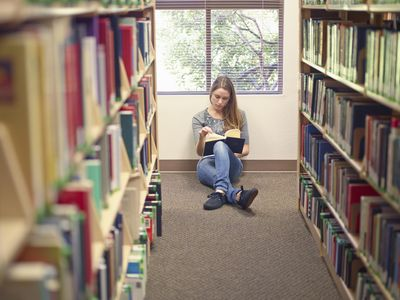 College student sitting on the floor in the library stacks studying