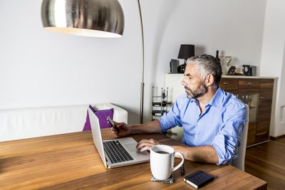 Man sitting in front of laptop looking at his phone