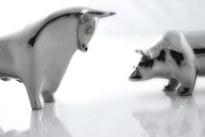 Silver statuettes of bull and bear markets facing-off indicating investing types.