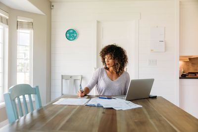 A young woman looks over her weekly financial plan.