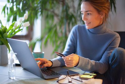 Woman holds credit card looking at a laptop