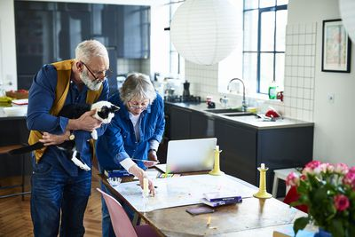 Retired couple planning a cross-country vacation in their kitchen