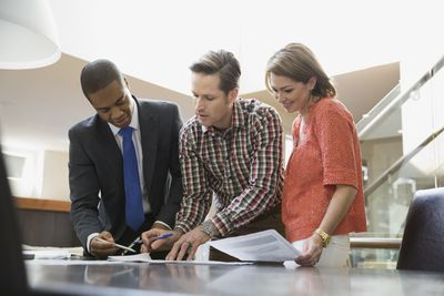 A couple reviews and signs paperwork with a financial advisor in an office