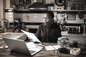 Woman doing finances with paperwork at a laptop in the evening