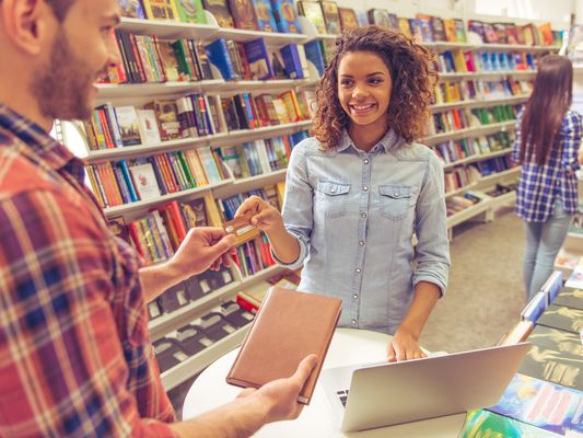 A young woman in a bookstore hands over a credit card to pay for a sleek notebook.