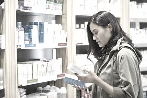 Customer comparing medicines by rack at pharmacy