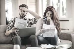 A stressed couple sits on a sofa worrying over their credit card statement