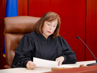 Female judge at the bench reading papers.