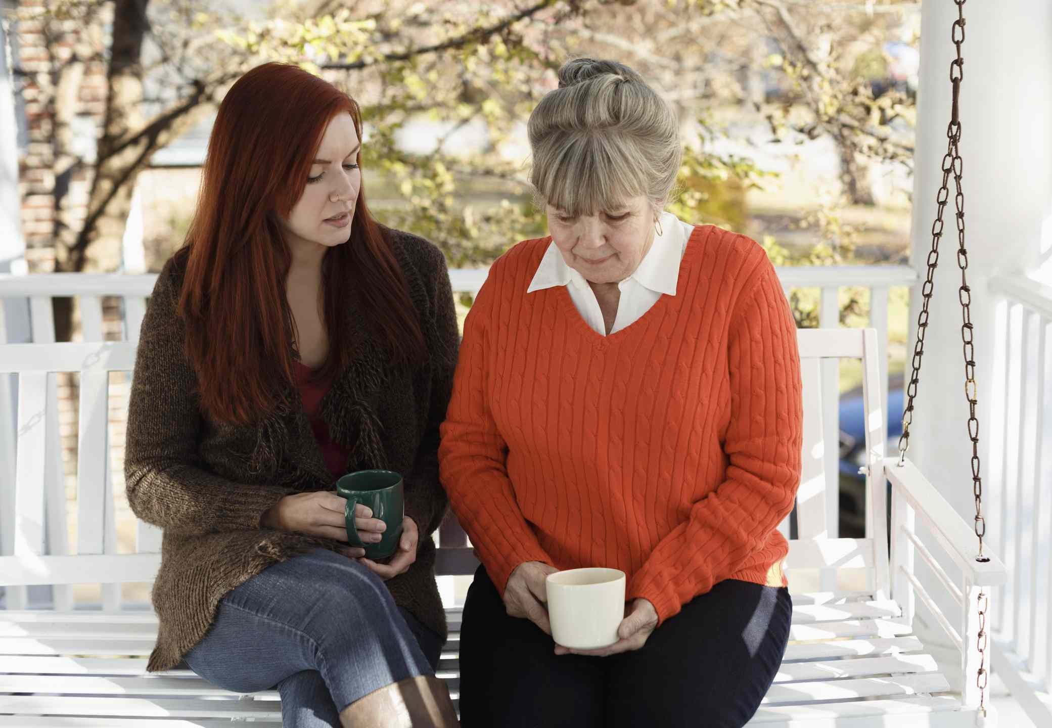 Women having serious discussion on porch swing
