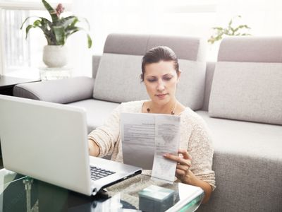A woman sitting on the floor in front of a laptop, looking at documents