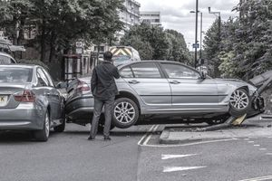 Man on cellphone watches car being towed after accident
