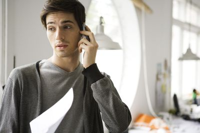 A man talks to his insurance agent on the phone.