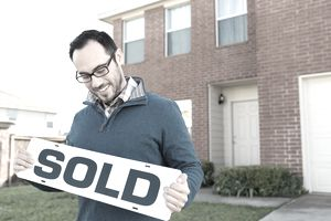 man holding sold sign in front of house