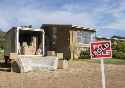 Sold sign and moving van outside house