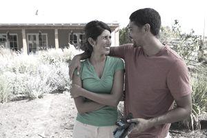 man and woman hugging outside home