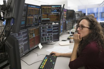 Stock trader sitting at a desk with multiple computer screens