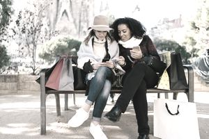Two friends in Barcelona sitting at bench after shopping