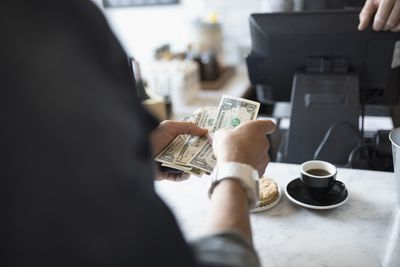 Customer paying with cash at cafe counter