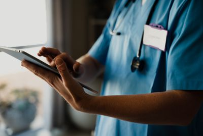 A medical professional wearing scrubs uses a touch screen tablet