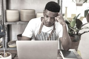 Small business owner thinking in front of laptop
