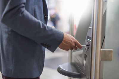 Midsection of man inserting debit card into atm