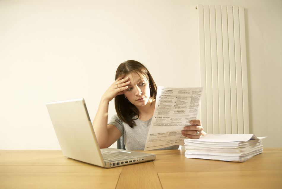 Woman sitting at a table looking at some paperwork stressed out