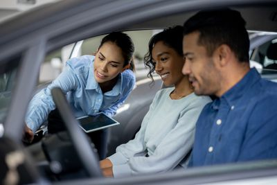 Saleswoman working at a dealership showing a car to a couple