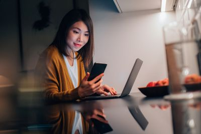 Young Asian woman looking at smartphone while working with laptop in the kitchen at home in the evening