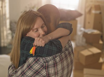 A young couple hugs in a room full of boxes in their new home.